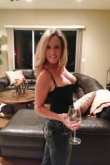 Busty blonde having a glass of wine.