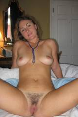 Spreading to show her hairy pussy