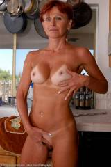 Hot redhead milf posing in her kitchen