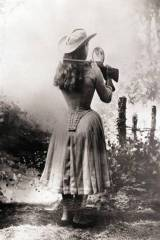 Annie Oakley shooting over her shoulder using a ha...